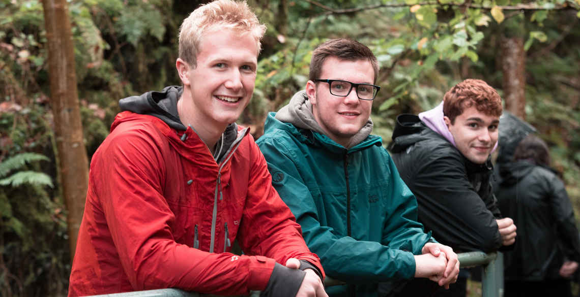 3 male students with forest backdrop