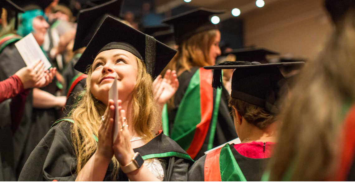 Female student smiling at graduation, clasping her hands together