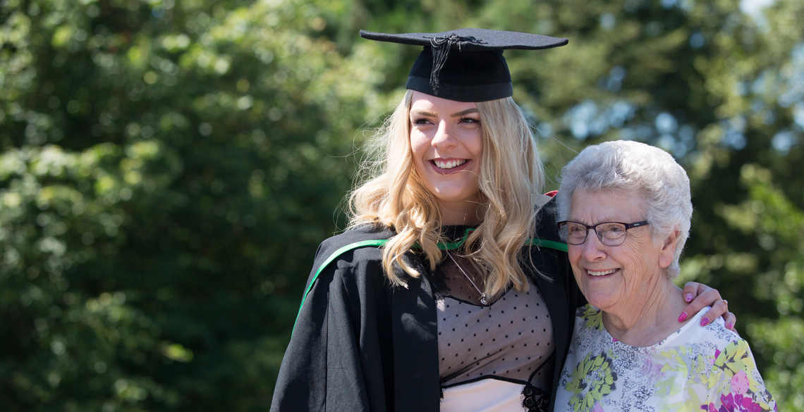 Female student in graduation gowns with her grandmother