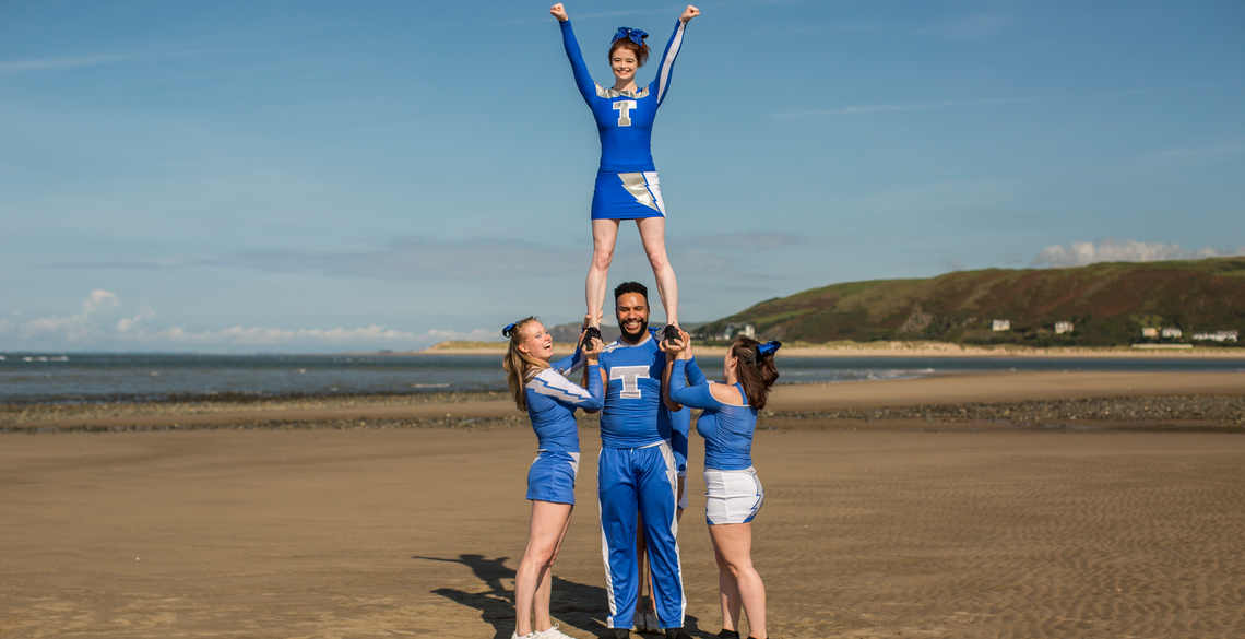 4 cheerleaders in pyramid position on the beach
