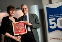 Professor M. Wynn Thomas, chairman of the Welsh Books Council, presents the award to Lynwen Rees Jones, director CES