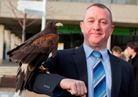 Aberystwyth University's Director of Health and Safety, Phil Maddison with Harris Hawk, 'Hope'.