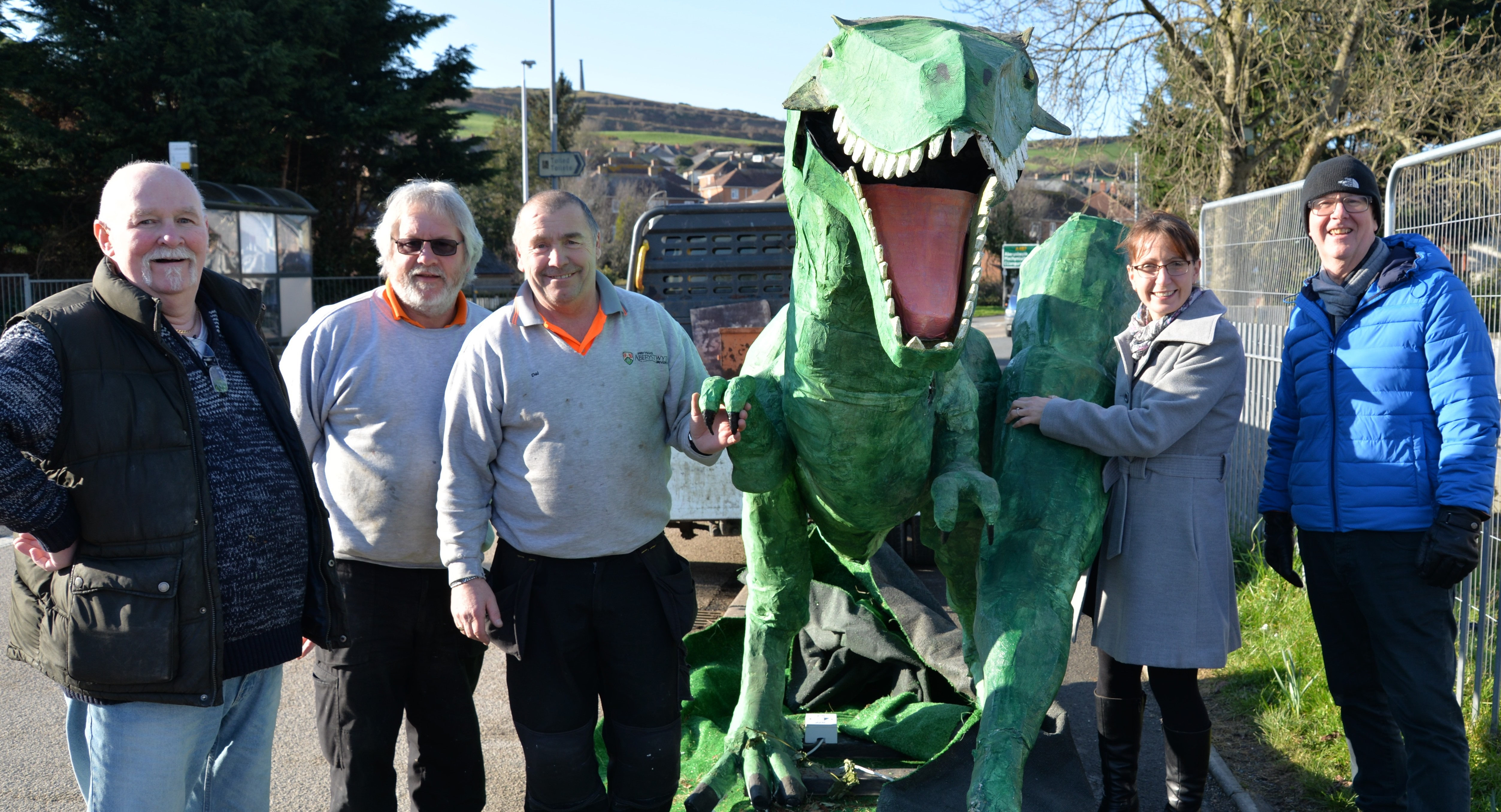 Dave the Dinosaur making his way from Penparcau Community Forum's offices to Old College accompanied by (left to right) George Barratt, Penparcau Forum, Jeff Dowse and Dai Gornall from Aberystwyth University's Property Services Team, Nia Davies, Aberystwyth University Old College Project and Bryn Jones, Penparcau Forum.