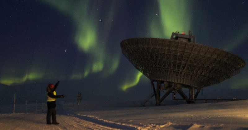 MPhys Physics with Planetary and Space Physics student Elliot Vale standing near the EISCAT radar on Svalbard with the aurora borealis in the night sky.