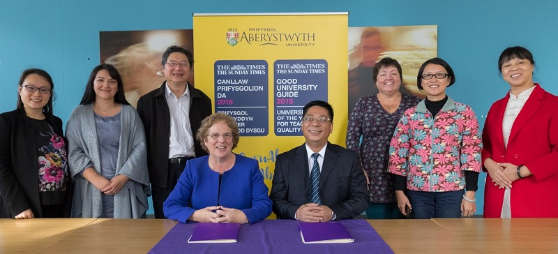 Professor Elizabeth Treasure, Vice-Chancellor Aberystwyth with Mr Xiao ZHENG, Chancellor of Wuyi University (seated) with representatives from the two universities at the signing of a Memorandum of Understanding.