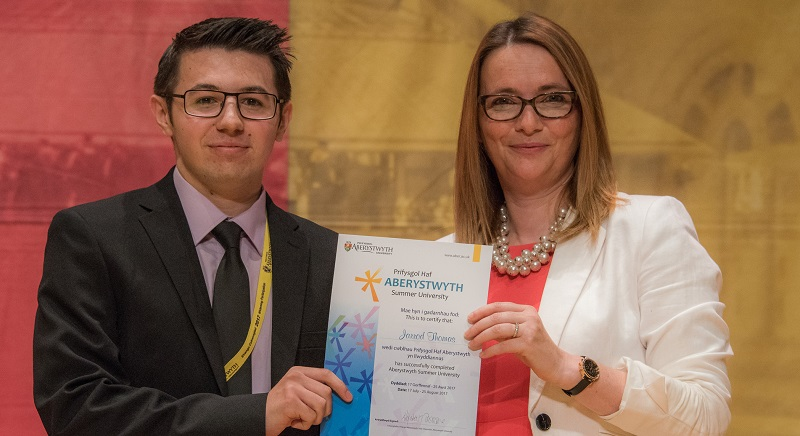 Jarrod Thomas being presented with his graduation certificate from the Aberystwyth Summer University by Kirsty Williams AM, Welsh Government Cabinet Secretary for Education, August 2017