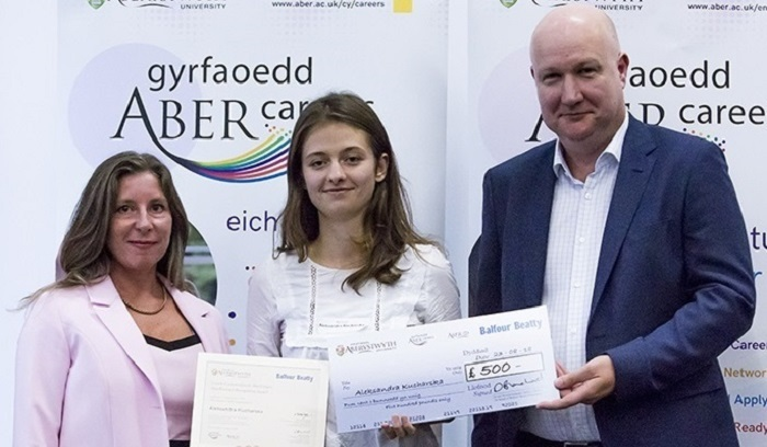 Aleksandra Kucharska (centre) receiving the Aber Forward Outstanding Achievement Award along with a cheque for £500 from David Blanchard, Balfour Beatty Investment Director, and Sian Furlong-Davies, Director of Careers Service at Aberystwyth University.