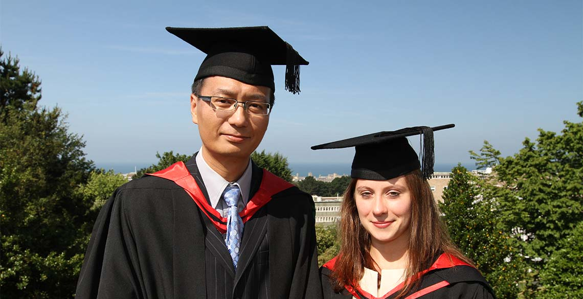 BA, BSc, MA, MSc, PhD - what do they all mean? Two Masters' students at graduation.