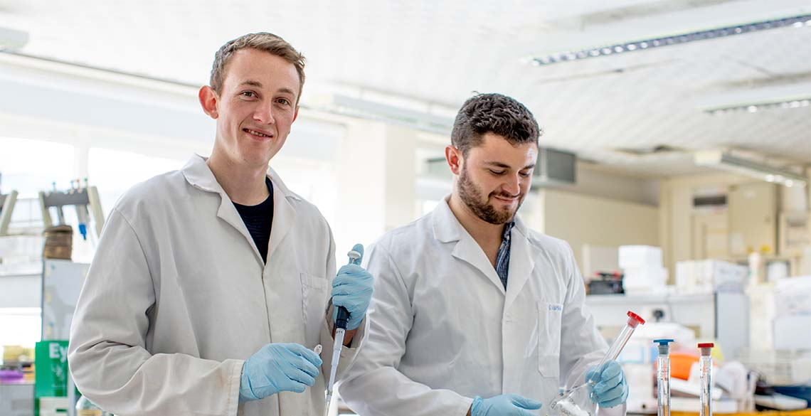 Why go to university? Two male students researching in a science lab