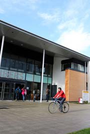 Photo of person cycling past a campus building