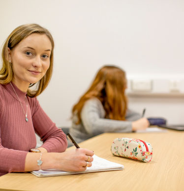 Photo of a student sat at a desk, writing