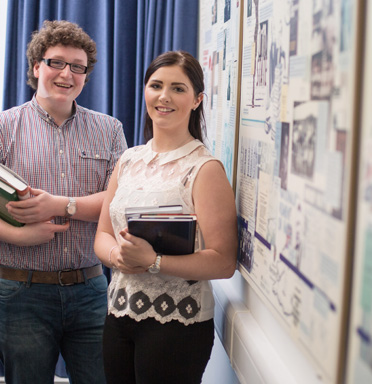 Photo of 2 students holding books